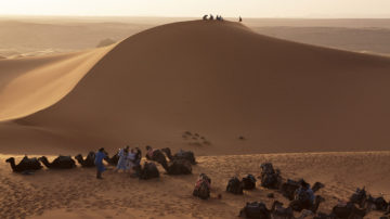 Tourists sitting on a dune in erg chebbi